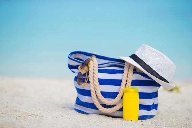Bolsa azul, sombrero de paja blanco, gafas de sol y botella de protector solar en playa tropical