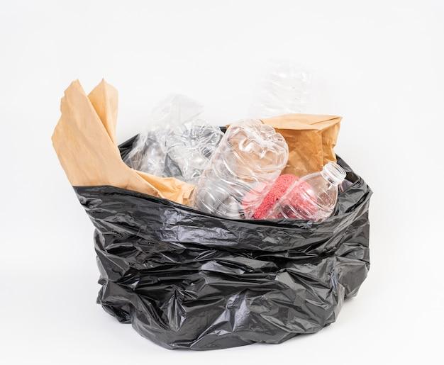 Bolsa de basura con basura de reciclaje sobre fondo blanco.