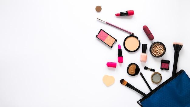 Bolsa de belleza con diferentes cosméticos en mesa blanca.