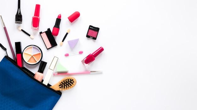 Bolsa de belleza con diferentes cosméticos en la mesa.
