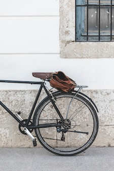 Bolsa en bicicleta aparcada cerca de la pared.