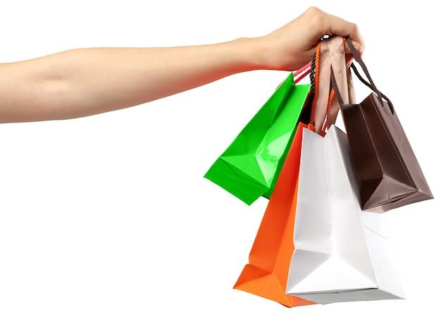 Bolsa de la compra. mano femenina que sostiene el bolso de compras en blanco