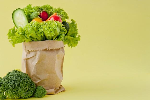 Bolsa de compras con comestibles sobre fondo amarillo