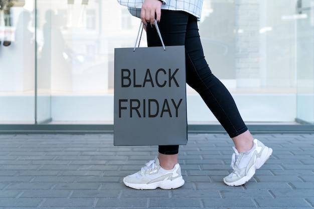Bolsa de compras con inscripción black friday en el espacio de las piernas femeninas. concepto de compras económicas.