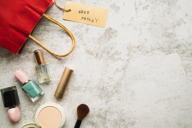 Bolsa de compras con poca etiqueta cerca de lápiz labial y esmalte de uñas