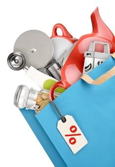 Bolsa de compras con utensilios de cocina aislado sobre fondo blanco.