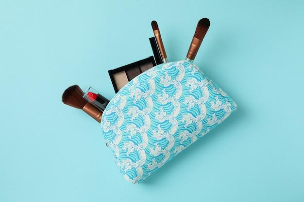 Bolsa de cosméticos con cosméticos sobre fondo azul.