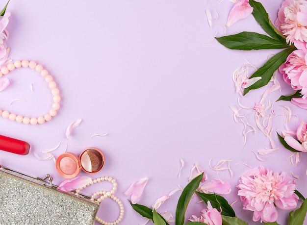 Bolsa de cosméticos femenina plateada abierta con lápiz labial rojo, sombras brillantes y pulseras hechas de perlas y un ramo de flores de peonía