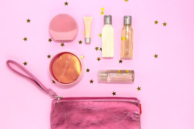 Bolsa de cosméticos con productos de maquillaje mujer sobre fondo con estrellas doradas.