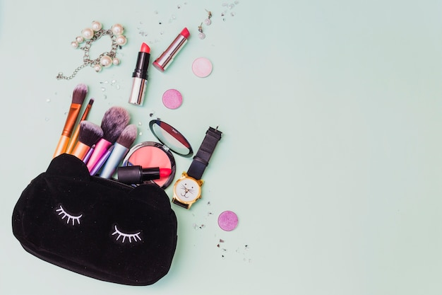 Bolsa de cosméticos con pulsera; reloj de pulsera y pendientes sobre fondo de color