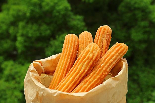 Bolsa de deliciosos churros fritos frescos con follaje verde borroso