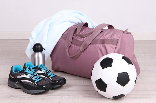 Bolsa de deporte con equipamiento deportivo en gimnasio.