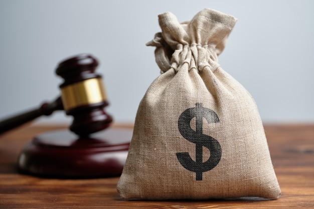 Bolsa de dinero al lado de un martillo juez