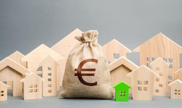 Bolsa de dinero en euros y una ciudad de figuras de casas. compra de bienes raíces, precio justo. presupuesto municipal de la ciudad.