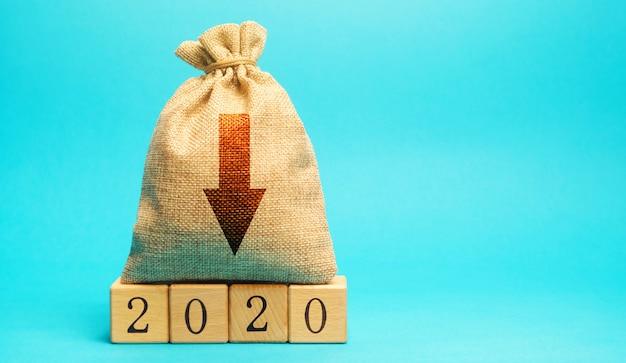 Bolsa de dinero con flecha hacia abajo y bloques de madera 2020. crisis económica y recesión.