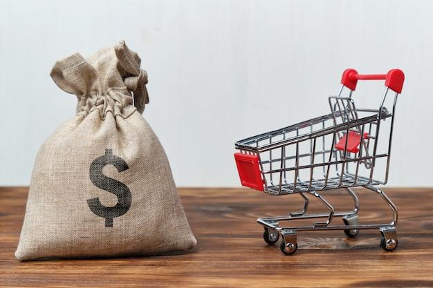 Bolsa de dinero junto a un carrito de la tienda