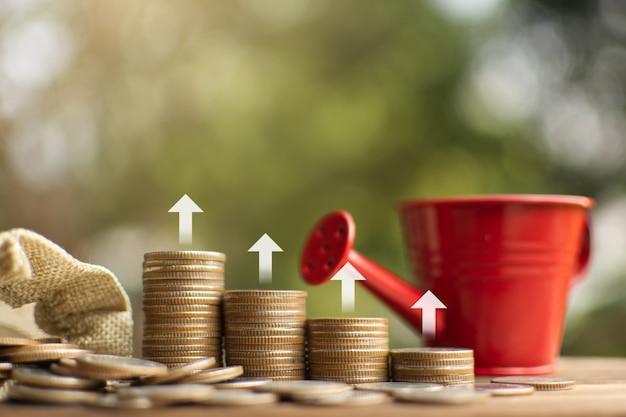 Bolsa de dinero y monedas dispuestas verticalmente, ahorro y creciente concepto de negocio.