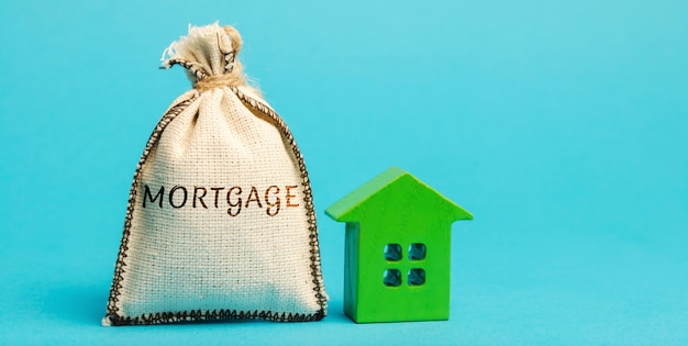 Bolsa de dinero con la palabra hipoteca y casa de madera.