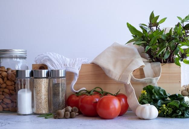 Bolsa ecológica y caja de madera de comida sana vegana en superficie de madera. compra y entrega de comestibles sin plástico.
