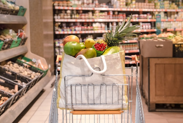Bolsa ecológica con diferentes frutas y verduras en un carrito de compras.