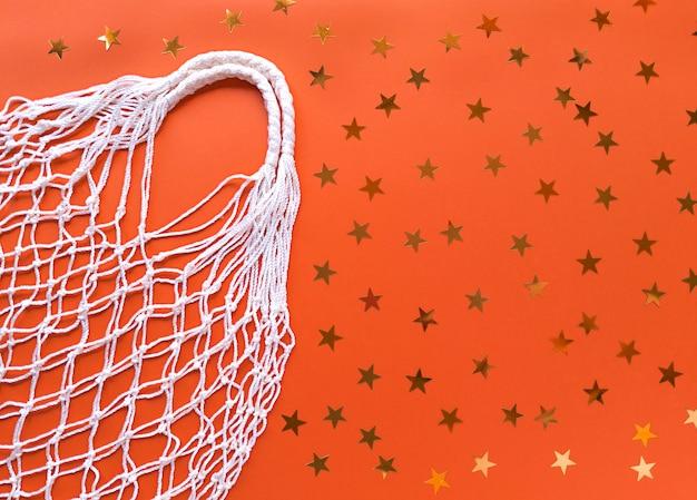Bolsa ecológica de hilo blanco de algodón sobre fondo naranja con decoración de estrellas doradas. plano simple con espacio de copia. concepto de ecología cero residuos.
