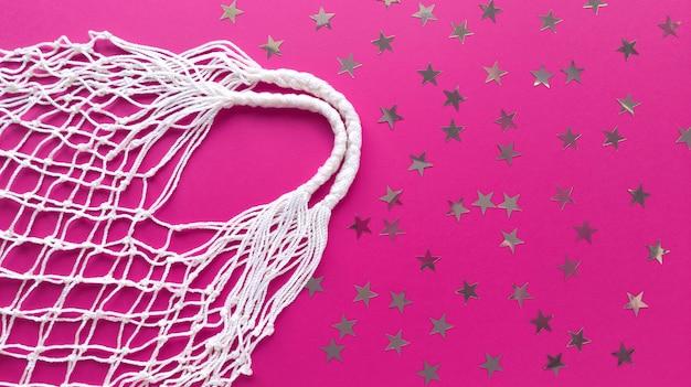 Bolsa ecológica de hilo blanco de algodón sobre fondo rosa con decoración de estrellas plateadas. plano simple con espacio de copia. concepto de ecología cero residuos.