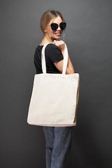 La bolsa ecológica para maqueta está sostenida por una mujer sobre textura gris