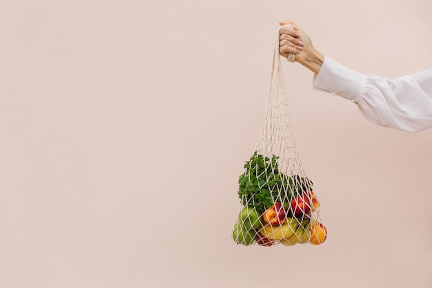 Bolsa ecológica reutilizable para compras. bolsa de compras de cadena con frutas en manos de una mujer joven