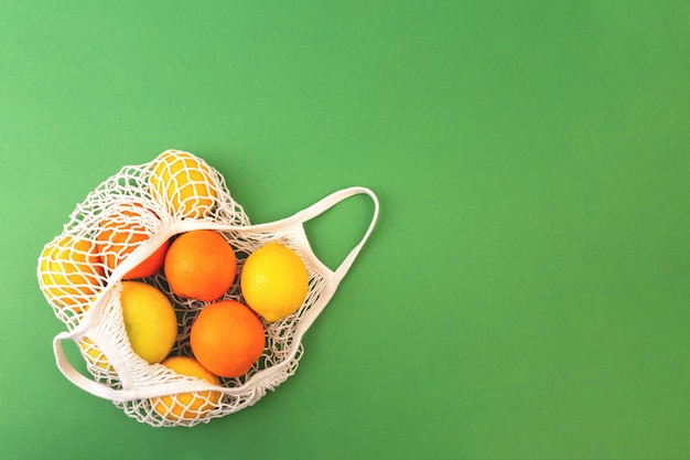 Bolsa de frutas reutilizables con naranjas y limones sobre fondo verde. concepto de cero residuos. lay flat, copia espacio.