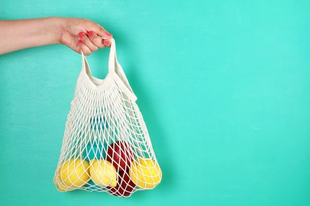 Bolsa de malla de compras reutilizable con limones, frutas y botella de vidrio. cero desperdicio, concepto de plástico libre.