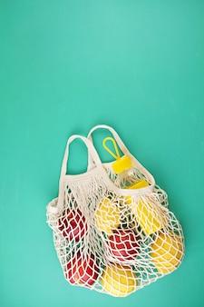 Bolsa de malla de compras reutilizable con limones, frutas y botella de vidrio.