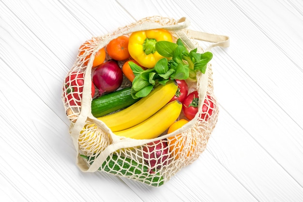 Bolsa de malla ecológica completa de diferentes alimentos saludables: pimiento, tomate, plátano, limón, verde, mandarina, pepino, cebolla sobre fondo blanco de madera