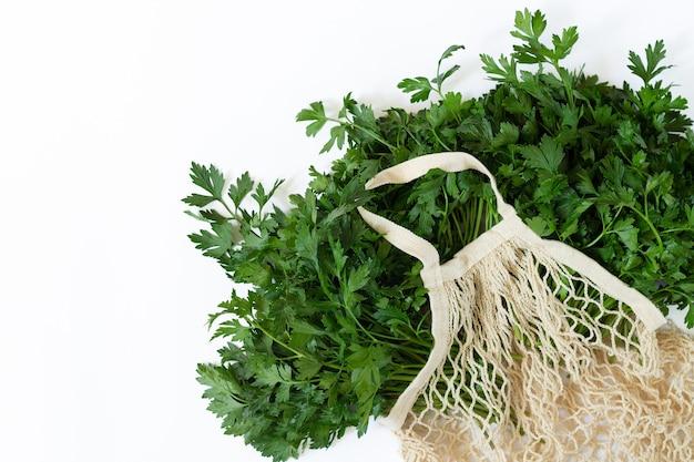 Bolsa de malla ecológica con perejil orgánico fresco aislado sobre fondo blanco desde arriba. espacio para texto