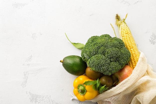 Bolsa de malla llena de diferentes alimentos saludables con espacio de copia. concepto de alimentación limpia o ecológica