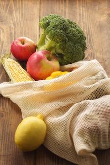 Bolsa de malla llena de diferentes alimentos saludables en la mesa de madera. concepto de alimentación limpia o ecológica
