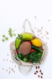 Bolsa de malla con vegetales ecológicos orgánicos aislados en la vista superior de fondo blanco. rechazo del plástico y el concepto de estilo de vida saludable