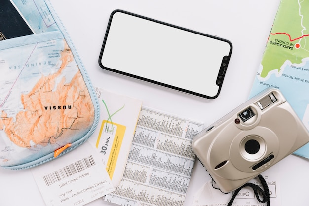 Bolsa; mapa; cámara digital y teléfono celular de pantalla en blanco sobre fondo blanco