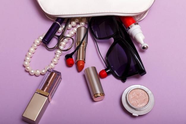Bolsa de maquillaje con cosméticos aislado sobre fondo morado
