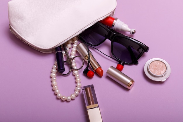 Bolsa de maquillaje con cosméticos aislado sobre fondo rosa