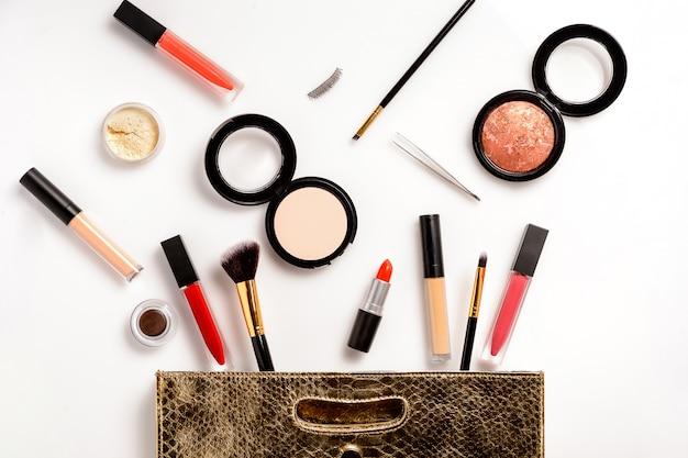 Bolsa de maquillaje de cuero, con productos de belleza cosméticos derramándose sobre fondo blanco.