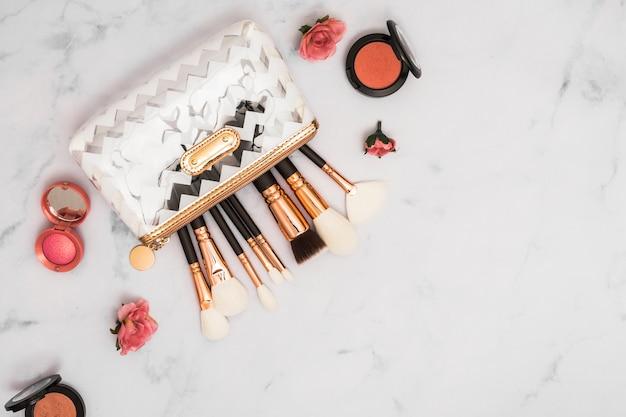 Bolsa de maquillaje profesional con pinceles y polvo compacto sobre fondo de mármol.