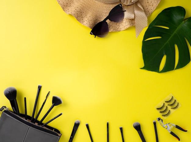 Bolsa de maquillaje con variedad de productos de belleza de fondo amarillo.