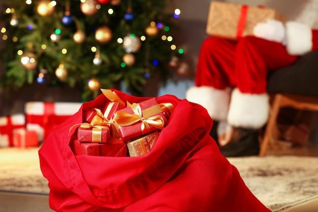 Bolsa de papá noel con regalos de navidad en la habitación