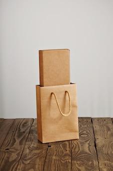Bolsa de papel artesanal con caja de cartón en blanco en el interior presentado en mesa de madera rústica, aislado sobre fondo blanco.