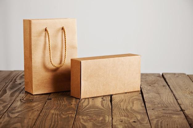 Bolsa de papel artesanal y caja de cartón en blanco presentada en mesa de madera rústica, aislado sobre fondo blanco.