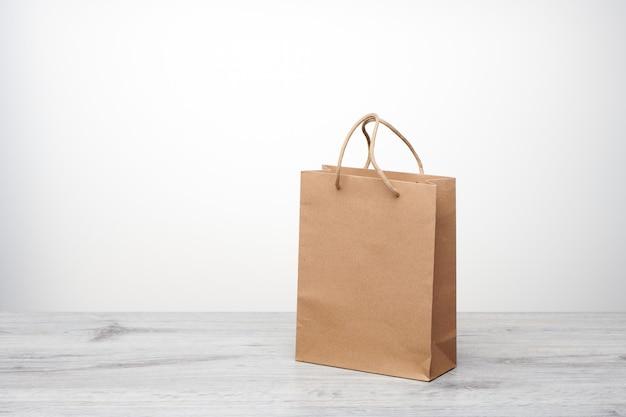 Bolsa de papel con asas aisladas. bolsa de papel kraft sobre mesa de madera.