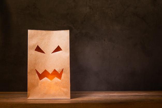 Bolsa de papel con cara de miedo en mesa de madera