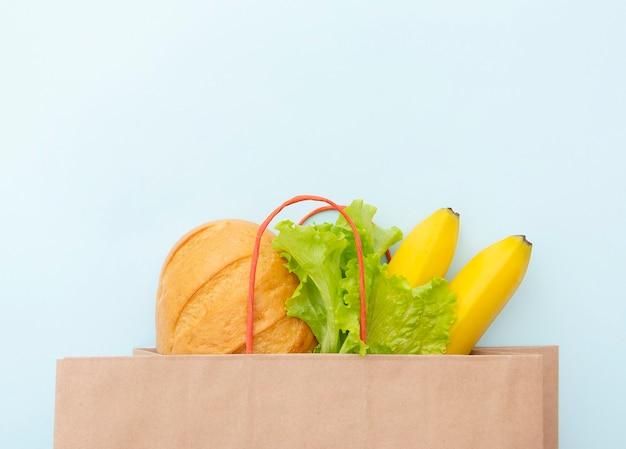 Bolsa de papel con comida: hojas verdes de ensalada, pan y plátano. disposición sobre fondo azul, vista superior