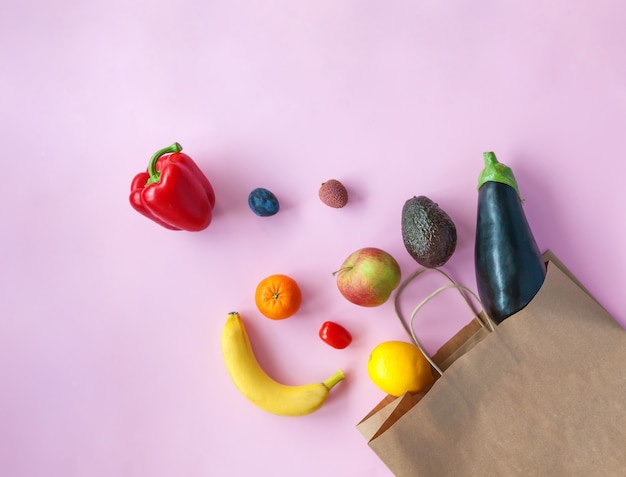 Bolsa de papel de compras con diferentes frutas y verduras cayendo de ella.