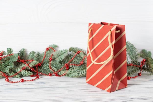 Bolsa de papel de compras navideñas con ramas de abeto decoradas con cuentas rojas